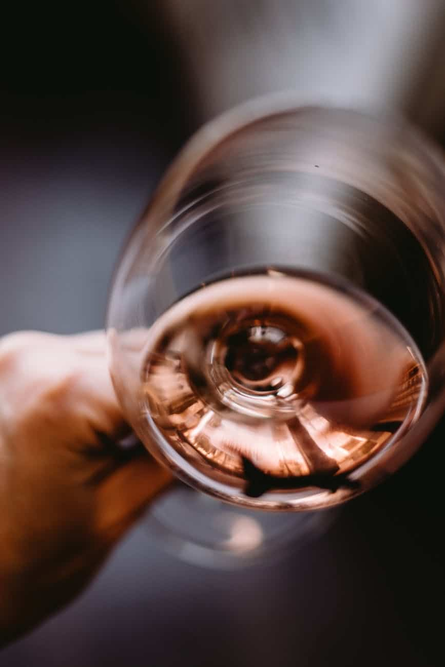 crop unrecognizable person holding glass of rose wine
