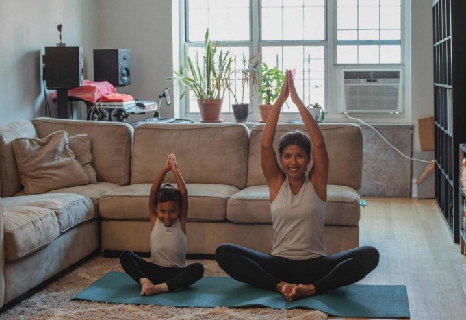 happy mother and daughter stretching together at home