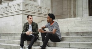 cheerful diverse men with coffee to go sitting on stairs