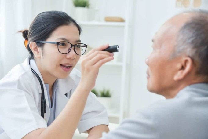 Female Doctor checking to senior man patient eyes.