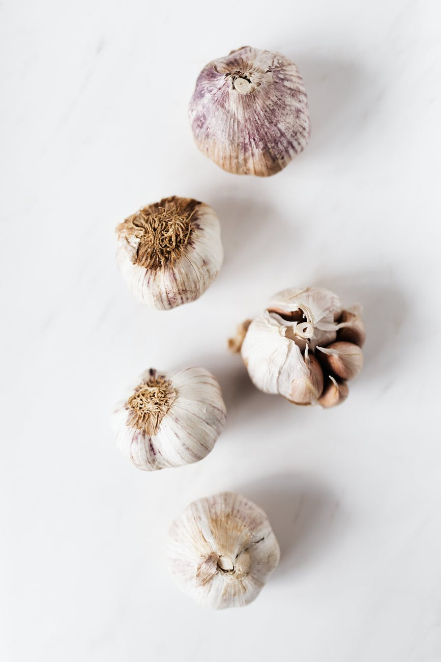 raw unpeeled garlic on marble surface