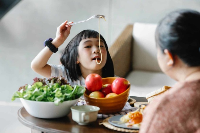 funny ethnic kid eating pasta during lunch with grandmother