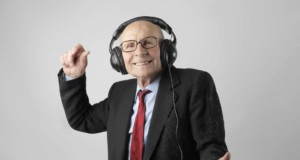 cheerful elderly man listening to music in headphones